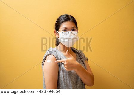 Asian Teen Girl Wearing Protective Mask Against Covid-19 With A Smile On His Face Shows The Vaccine