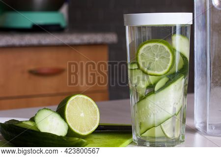 Cucumber And Lime Slices Are Filled With Water In A Glass. Cooking Water Infused With Lime And Cucum