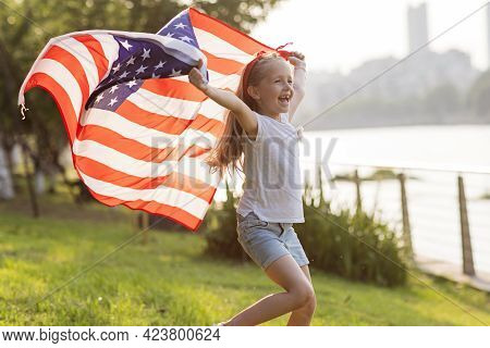 Patriotic Holiday. Happy Family, Mother And Daughter With American Flag Outdoors On Sunset. Usa Cele