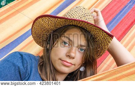 Portrait Of A Cute Girl In A Straw Hat Lying In A Hammock, A Cute Young Cowgirl, Relaxing In The Sum