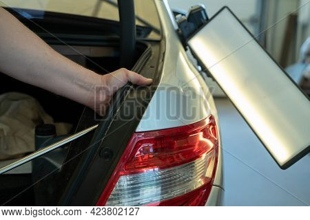 Process Of Paintless Dent Repair On Car Body. Technician S Hands With Puller Fixing Dent On Rear Car