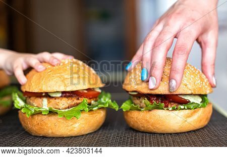 Small Childs Hand And Mothers Hand On Homemade Homemade Burgers. The Concept Of Cooking Delicious Fo