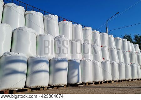 Group Of White Big Bags With Chemical Fertilizers In A Warehouse Outdoors. Stack Of Sacks In A 3 Row