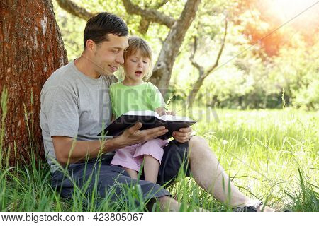 Happy Father With A Child Reading A Book On The Nature Of The Bible