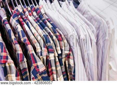 Long Sleeve Shirts Hanging On Hangers In A Clothing Store. Close-up