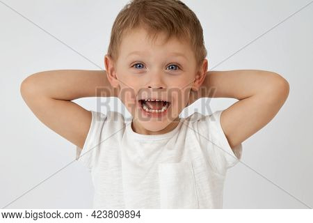 A Happy Child With Blue Eyes Threw His Hands Behind His Head On A White Background. The Boy Smiles A