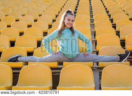 Stretch And Flex For Your Health. Flexible Tween Do Splits On Stadium Seats. Leg Stretch