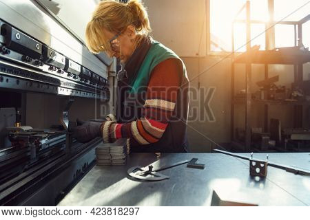 woman working in a modern factory and preparing materia for a CNC machine.