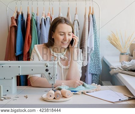 Positive Young Woman Dressmaker Working At Own Fashion Atelier, Smiling Happy Seamstress Talking On
