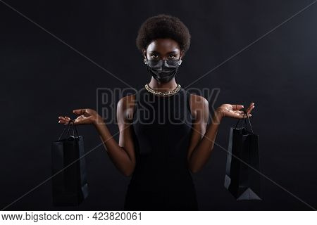 African American Woman In Black Medical Face Mask Holds Black Shopping Bags. Safety On Black Friday