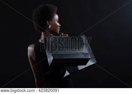 African American Woman With Afro Hairstyle Holds Black Shopping Bags. Sale And Discounts On Market A