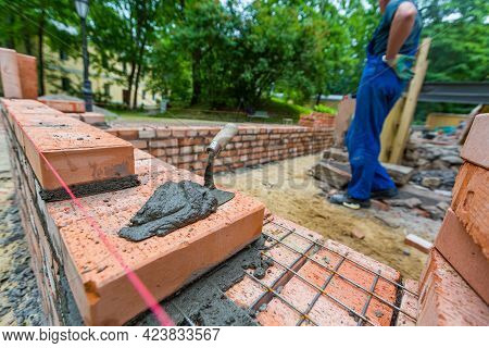 Putty Knife With Cement And Bricklayer Is Near Brickwork On Exterior Wall On Construction Site.