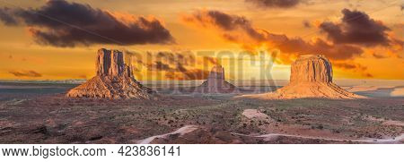 Beautiful dramatic sunset over the West and East Mitten Buttes in Monument Valley. Utah, USA. Panoramic photo