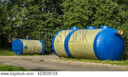 Two Huge Blue Containers For Collecting Sewage Waste Lie On The Grass