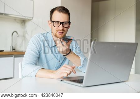Smart Young Man Sits At The Kitchen Desk And Works Remotely From Home, Using Laptop Computer And Rec