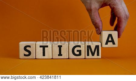 Stigma Symbol. Doctor Holds Cubes With The Word 'stigma'. Beautiful Orange Background. Psychological