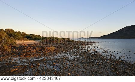 Sunrise Warmth Over A Rocky Beach At Low Tide On The Coral Sea At Cape Gloucester Queensland Austral