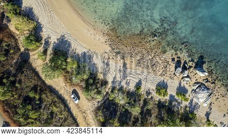 Drone Aerial Top Down View Of A Car Parked On A Dirt Road In Tropical Bushland Beside A Beach With T