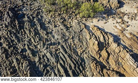 Close Up Of The Texture Of Rocks On A Stoney Coastal Beach At Low Tide Overhead Aerial View