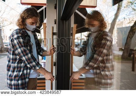 Young white cafe worker in face mask opening door outdoors