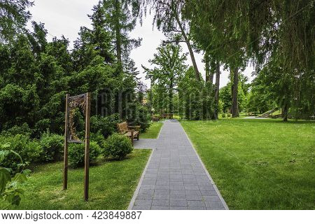 Stone Paved Pathway With Green Lawns And Tree On Both Sides In Park