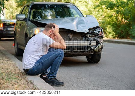 Car Accident. Man Holding His Head After Car Accident. Man Regrets Damage Caused During Car Wreck. M