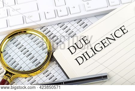 Due Diligence Text On The Notebook With Chart, Magnifier,keyboard And Pen