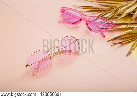 Pink Gold Colored Stylish Sunglasses On Color Summer Background With Gold Palm Leaves. Fashionable T