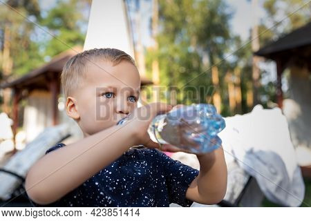 Portrait Of Cute Playful Little Caucasian Blond Thirsty Toddler Boy Kid Holding Plastic Bottle And D