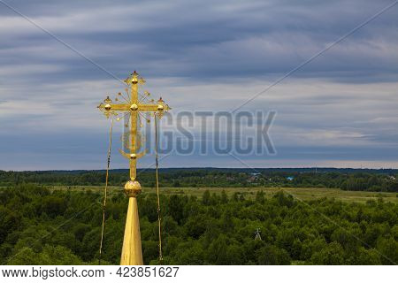 Gilded Orthodox Cross Against The Background Of A Cloudy Sky.