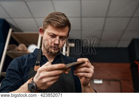 Leather Craftsman Checks A Product In A Workshop, Small And Medium-sized Businesses, A Family Busine