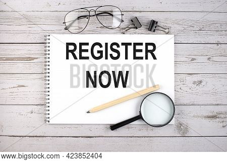 Notebook With Text Register Now On Wooden Table With Pen, Magnifier And Glasses
