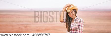 Cowgirl woman smiling happy on country farm landscape wearing cowboy hat. Beautiful young multiracial Asian American girl in panoramic countryside.