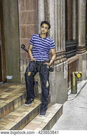 Dressing In  A Singlet, A Fashionable Pants, A Young Asian Teenager Is Leaning On A Doorway And Into