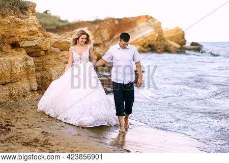Lovely Young Bride And Groom Walk Along The Sandy Rocks Along The Sea. Handsome Groom Holds The Hand