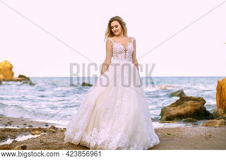 A Beautiful Bride In A White Wedding Dress Stands On The Shore Of The Ocean And Sandy Rocks On The W