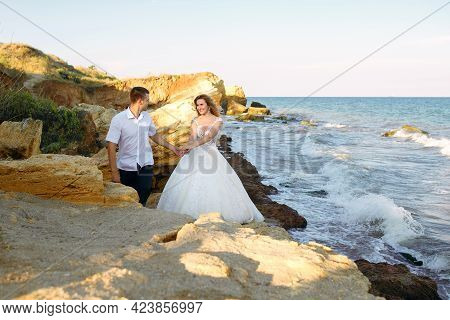 Lovely Bride And Groom Walk Along The Rocks Along The Sea On Their Wedding Day. Handsome Groom Holds