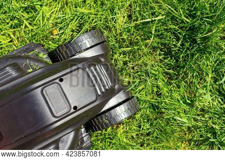 Close-up And Top View Of A Black Lawn Mower In The Backyard With Green Grass Grown Up. Summer Garden