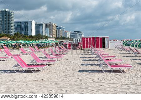 Chaise Lounges In Miami, Usa. Pink Chaise Lounges On Beach In Row. Beach Furniture. Summer Vacation