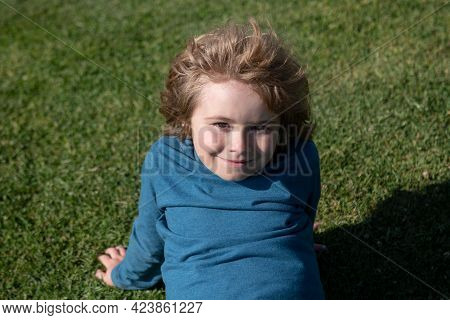 Portrait Of A Cute Child Boy On Grass In Park. Close Up Caucasian Kids Face. Closeup Head Of Funny K