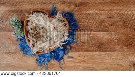 Beautiful stylized small furniture bed in heart shape with fur and lavander flowers for newborn photoshoot. Designed decoration object for infant studio photo on wooden background