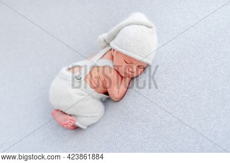 Newborn baby boy wearing knitted pants and hat sleeping on his tummy and holding tiny hands under his cheeks. Adorable infant child napping in studio with light blue colors