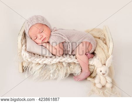 Newborn baby boy wearing knitted beige costume and hat sleeping on his tummy in small designed bed and holding tiny hands under his cheeks. Adorable infant child napping