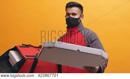 Delivery Boy Wearing Mask Carrying Pizza Boxes In His Red Parcel Box. Holding A Pizza Box In His Han