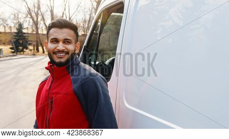 Young Indian Guy Standing On The Road With A White Van Behind Him. Delivery Guy Wearing Red Uniform