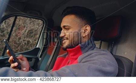 Young Delivery Guy Sitting In The Front Seat Of The Van With Hand On Steering. Holding A Phone In Hi