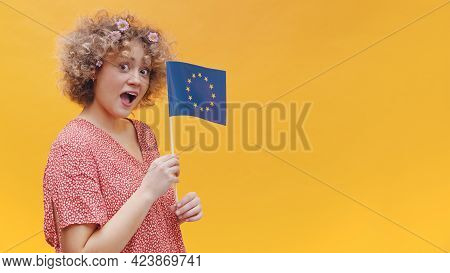 Beautiful Young Girl Holding A Small European Union Flag In Her Hand. Astonished Girl Wearing Casual