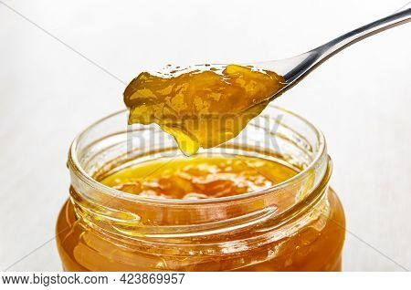 Metallic Spoon With Orange Jam Above Transparent Glass Jar With Jam On Wooden Table