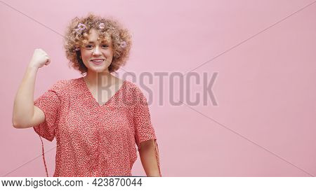Beautiful Confident Girl Making A Fist Showing Girls Power. Girl Dressed In Pink Shirt. Studio Shot