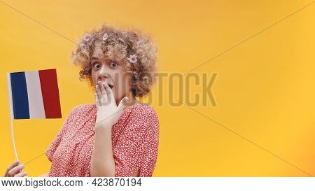 Attractive Girl Holding A Small France Flag In Her Hand. Astonished Girl Isolated Shot With Yellow B